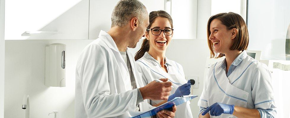 Three dental team members laughing together in dental office